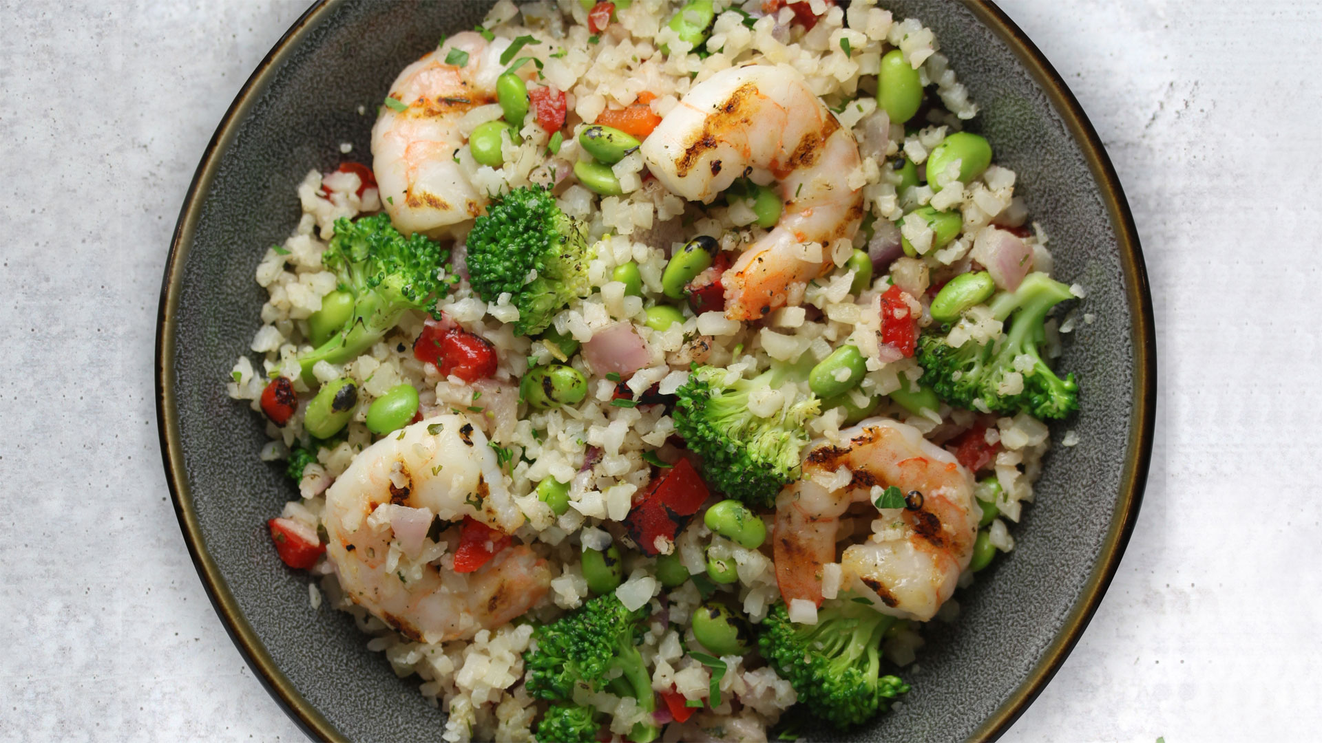 Featuring Haliburton Sesame Citrus Riced Cauliflower, Fire Roasted Red Bell Pepper, Red Onion, Mukimame, Broccoli and Grilled Shrimp.